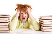 Student mellan två högar av böcker som skriker — Stockfoto