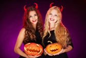 Witches with horns and Halloween pumpkins — Stock Photo