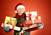 Man in Santa cap with giftboxes — Stock Photo