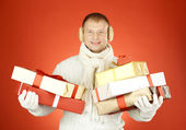 Man in winterwear with stack of giftboxes — Stock Photo