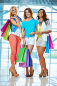 Girlfriends with paperbags standing in the mall — Stock Photo