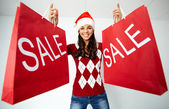 Girl in Santa cap holds paperbags with symbol of sale — Stock Photo