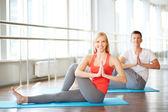Woman doing yoga exercise with guy — Stock Photo