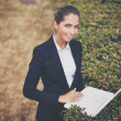 Businesswoman with laptop networking in park — Stock Photo #36816397