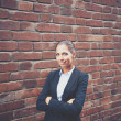 Businesswoman standing by brick wall  — Stock Photo