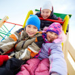 Happy friends having fun on playground in winter — Stock Photo