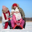 Happy kids sitting on sledge with their parents — Stock Photo