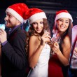Friends in Santa caps holding flutes of champagne — Stock Photo