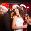 Friends in Santa caps dancing — Stock Photo