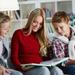 Family reading book on Christmas evening — Stock Photo