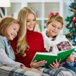 Woman and her two children reading book on Christmas evening — Stok fotoğraf