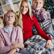 Woman and her two children reading book on Christmas evening — Foto Stock