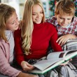 Woman and her two children reading book on Christmas evening — Stock Photo