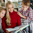 Woman and her two children reading book on Christmas evening — Foto de Stock   #36817765