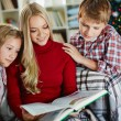 Woman and her two children reading book on Christmas evening — Stock Photo #36817765