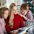 Woman and her two children reading book on Christmas evening — Foto de Stock   #36817771
