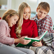 Woman and her two children reading book on Christmas evening — ストック写真