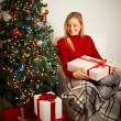 Girl with big giftbox looking at heap of presents — Stock Photo