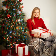 Smiling girl with red giftbox by decorated xmas tree — Stock Photo