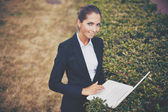 Businesswoman with laptop networking in park — Stock Photo