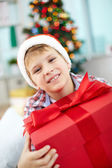 Cheerful boy with big red giftbox — Stock Photo