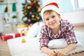 Cheerful boy lying on the floor on Christmas — Stock Photo