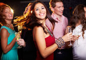 Cheerful girl with champagne flute dancing — Stock Photo