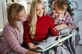 Woman and her two children reading book on Christmas evening — Stockfoto