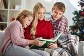 Mulher e seus dois filhos lendo livro na noite de natal — Foto Stock