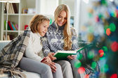 Woman and daughter reading book on Christmas evening — Stockfoto