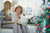 женщина и дочь читать книгу на рождественский вечер — Стоковое фото