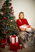 Girl with big giftbox looking at heap of presents — Stockfoto