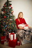 Smiling girl with red giftbox by decorated xmas tree — Stockfoto