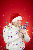 Joyful man in Santa cap with confetti cracker — Stock Photo