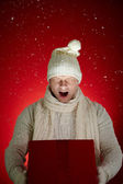 Man in winterwear holding open giftbox — Stock Photo
