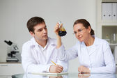 Scientists looking at glass flask with liquid oil — Stockfoto