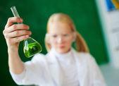 Green liquid held by schoolgirl — Stock fotografie