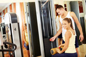 Female in gym with young trainer — Stock Photo