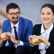 Colleagues eating sandwiches — Stock Photo