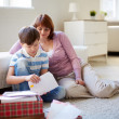 Boy opening envelope with his mother — Stock Photo