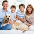 Stock Photo: Cheerful family with their pet