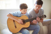 Man teaching his son how to play guitar — Stock Photo