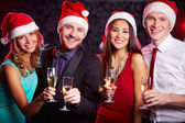 Friends in Santa caps holding champagne — Stock Photo