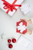Christmas present on palms — Stock Photo
