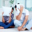 Stock Photo: Guy and girl with pillows by faces