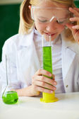 Schoolgirl smelling chemical tube — Stock Photo