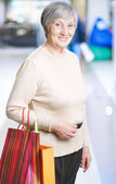 Mature woman with shopping bags — Stock Photo