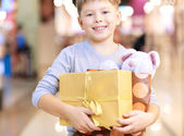 Child holding paperbag and giftbox — Stock Photo