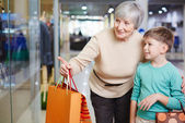 Child and his grandmother with paperbags — Stock Photo