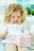 Girl unwrapping present — Stock Photo